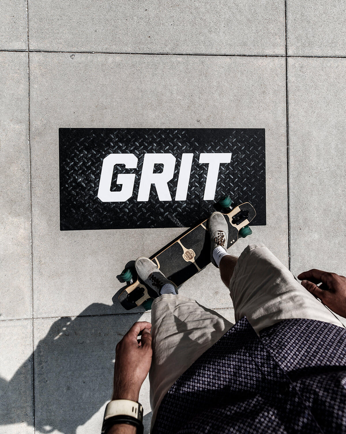 Student standing on skateboard above Grit branding statement