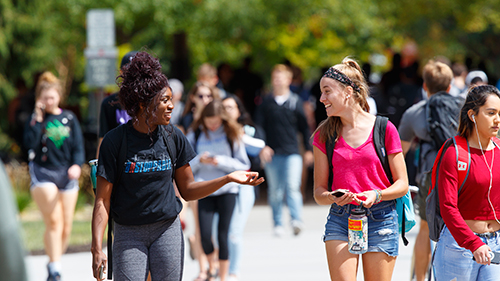 Two female students talking while walking to class on a sunny day.