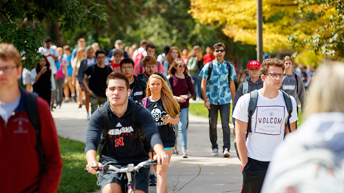 Students walking and biking to class on a sunny day.